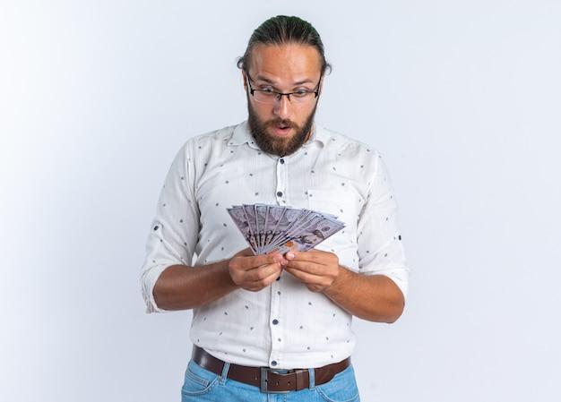 Удивленный взрослый красавец в очках, держащий и смотрящий на деньги, изолированные на белой стене с копией пространства