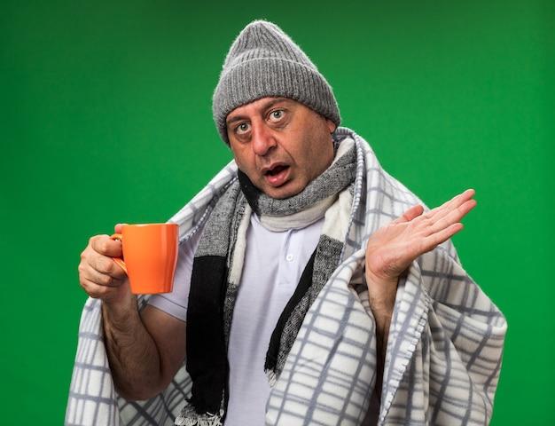 Sorpreso adulto malato uomo caucasico con sciarpa intorno al collo indossando cappello invernale avvolto in plaid tazza di contenimento e tenendo la mano aperta isolata sulla parete verde con spazio di copia