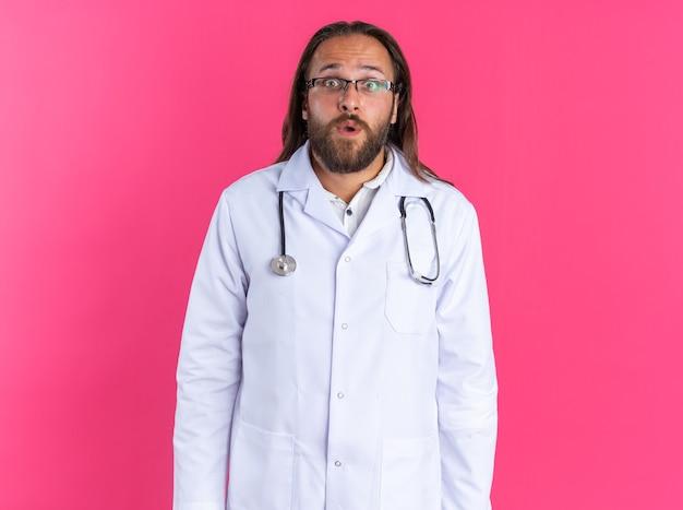분홍색 벽에 격리된 카메라를 바라보는 안경을 쓰고 의료 가운과 청진기를 착용한 놀란 성인 남성 의사