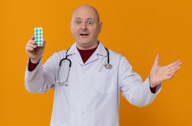 Uomo adulto sorpreso in uniforme da medico con stetoscopio che tiene in mano un blister di medicinali e tiene la mano aperta