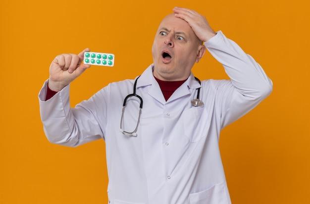 Удивленный взрослый мужчина в медицинской форме со стетоскопом, держащий и смотрящий на блистерную упаковку с лекарствами, положив руку ему на голову