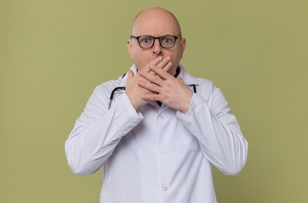 Uomo adulto sorpreso con gli occhiali in uniforme da medico con stetoscopio che si mette le mani sulla bocca e guarda