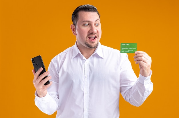 Surprised adult slavic businessman holding phone and looking at credit card
