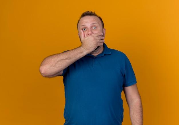 Удивленный взрослый славянский мужчина, прикрыв рот рукой