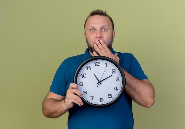 Удивленный взрослый славянский мужчина держит часы, положив руку на рот, глядя