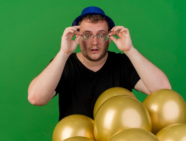 Surprised adult slavic man holds and looks through optical glasses wearing blue party hat standing with helium balloons