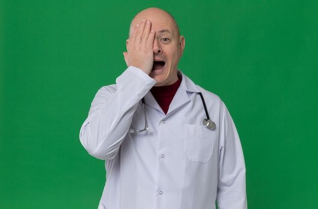 의사 제복을 입은 놀란 성인 슬라브 남자, 손으로 눈을 덮고 있는 청진기
