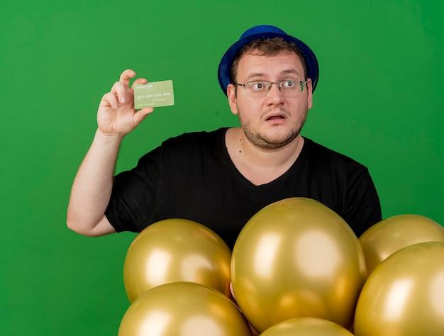Удивленный взрослый славянский мужчина в оптических очках в синей праздничной шляпе держит гелиевые шары и кредитную карту