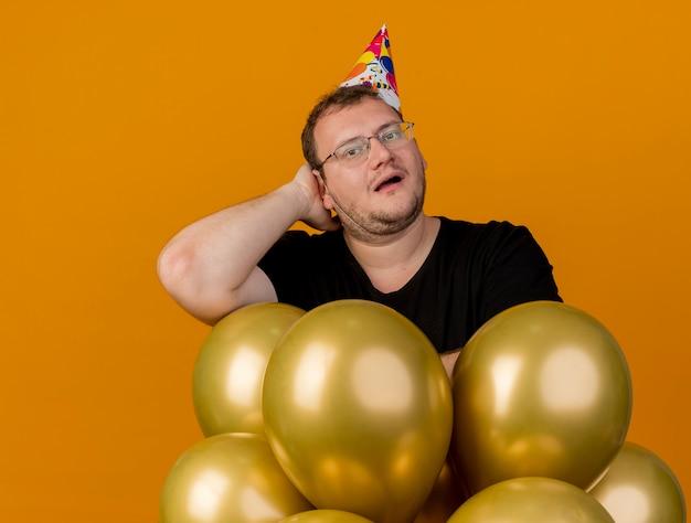 Sorpreso uomo slavo adulto in occhiali ottici che indossa il berretto di compleanno mette la mano sulla testa dietro e si alza con palloncini di elio