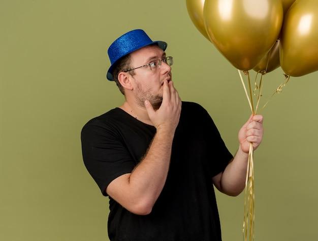 Sorpreso uomo slavo adulto in occhiali ottici che indossa un cappello da festa blu tiene e guarda palloncini di elio