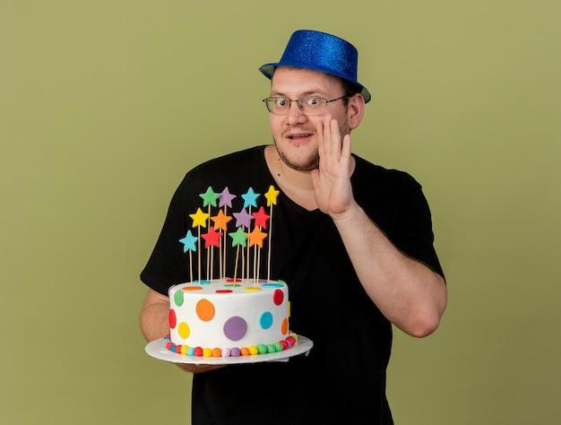 L'uomo slavo adulto sorpreso in occhiali ottici che indossa un cappello da festa blu tiene la mano vicino alla bocca e tiene la torta di compleanno guardando la fotocamera