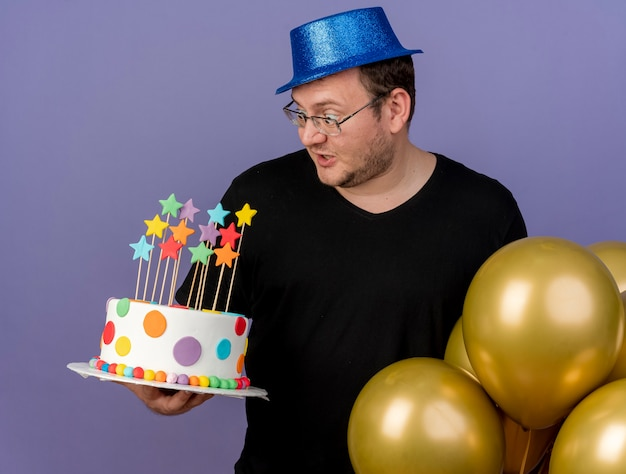 Surprised adult slavic man in optical glasses wearing blue party hat looks at birthday cake standing with helium balloons