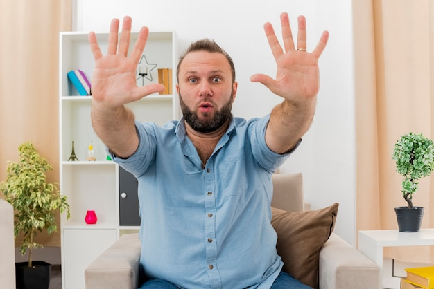 놀란 성인 슬라브 남자는 거실 안에 두 손을 들고 안락 의자에 앉아