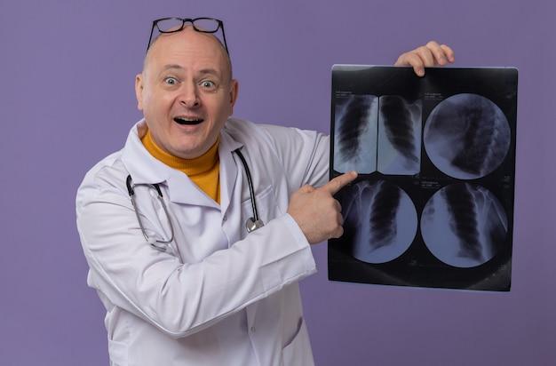 Uomo slavo adulto sorpreso con occhiali ottici in uniforme da medico con stetoscopio che tiene e punta al risultato dei raggi x