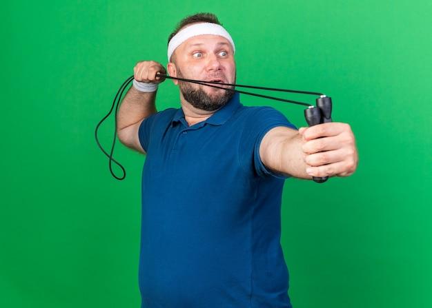 Удивленный взрослый славянский спортивный мужчина с повязкой на голову и браслетами держит скакалку и смотрит в сторону, изолированную на зеленой стене с копией пространства