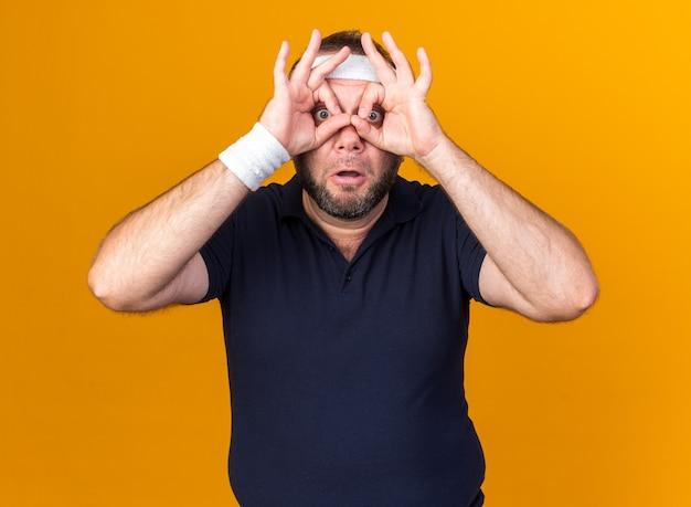복사 공간 오렌지 벽에 고립 된 손가락을 통해 찾고 머리띠와 팔찌를 입고 놀란 성인 슬라브 스포티 한 남자