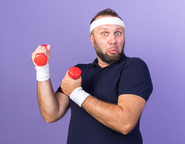 Sorpreso adulto slavo sportivo uomo che indossa fascia e braccialetti tenendo manubri isolati sulla parete viola con spazio di copia