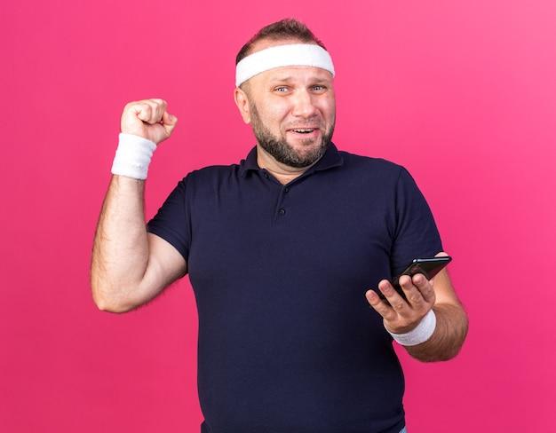 Sorpreso adulto slavo sportivo uomo che indossa fascia e braccialetti tenendo il telefono e tenendo il pugno in alto isolato sulla parete rosa con spazio di copia