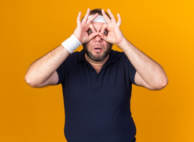Surprised adult slavic sporty man wearing headband and wristbands looking  through fingers isolated on orange wall with copy space