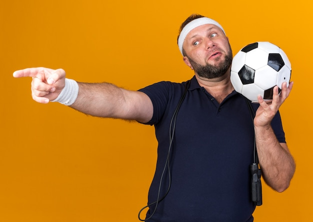 Surprised adult slavic sporty man with jumping rope around neck wearing headband and wristbands holding ball and pointing at side isolated on orange wall with copy space