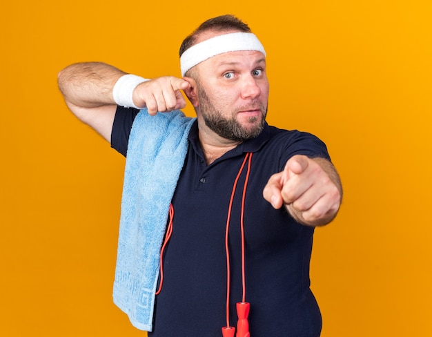 Surprised adult slavic sporty man with jumping rope around neck and with towel on shoulder wearing headband and wristbands pointing  isolated on orange wall with copy space