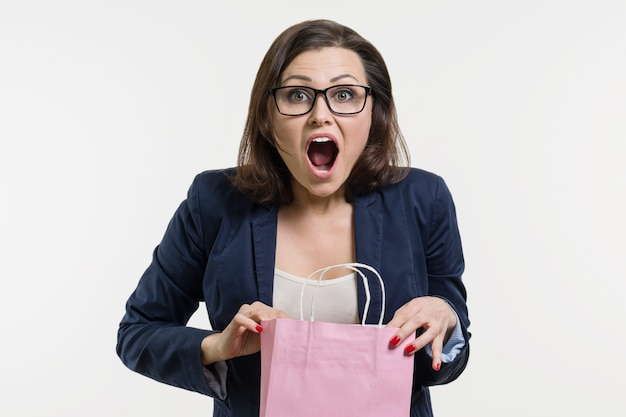Surprised adult woman looking shopping bag