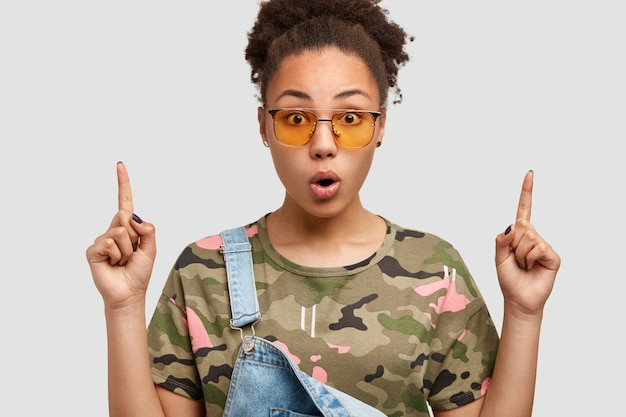 カジュアルなカモフラージュtシャツとデニムのオーバーオールを着たトレンディな色合いの驚いたアフリカ系アメリカ人の女性、両方の人差し指を上に向けたポイントは衝撃的な表情をしています