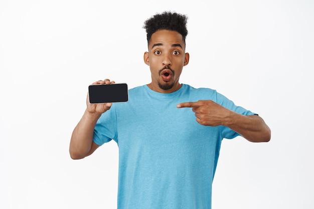 Sorpreso uomo afroamericano senza fiato dire wow, puntando il dito sullo schermo del telefono cellulare con faccia stupita, mostrando pubblicità su bianco