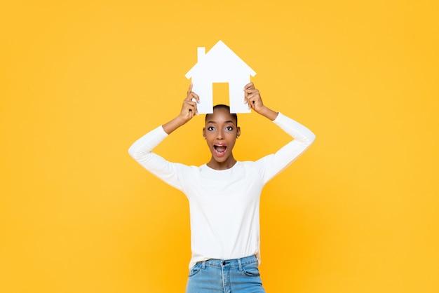 Удивленная женщина афроамериканца держа знак дома надземный изолированный на желтой стене
