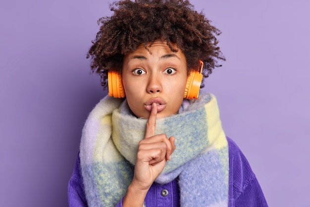 Surprised african american woman presses index finger to lips makes silence gesture tells secret wears warm scarf around neck listens music via wireless headphones.