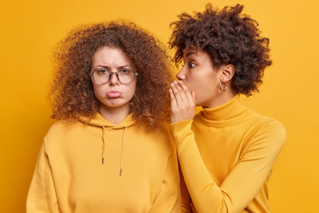 Surprised african american woman whispers secret information on ear of best friend who looks with gloomy expression spread rumors tells private news isolated over yellow wall. secrecy concept
