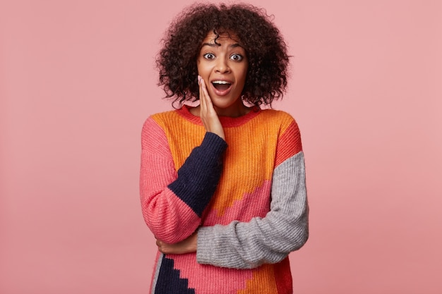 Surprised african american woman with an afro hairstyle with amazement looks, palm holds her cheek, feels impressed, looks affected excited overwrought, isolated
