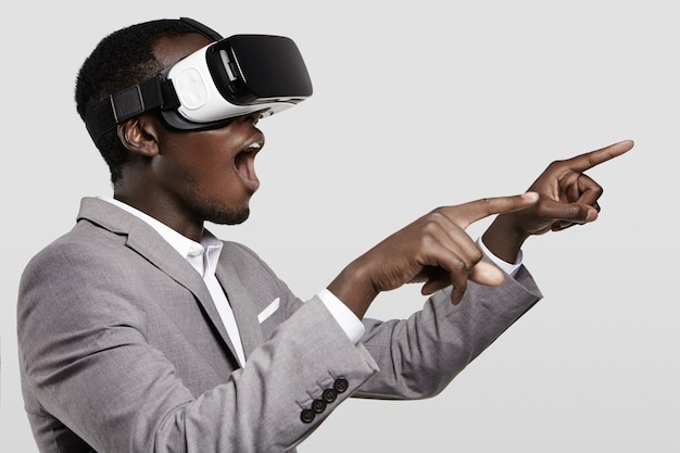 Surprised african businessman using oculus rift headset, experiencing virtual reality while playing video game.