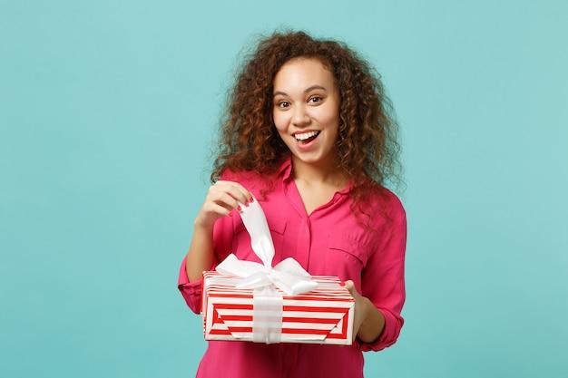 La ragazza africana sorpresa in vestiti rosa tiene la scatola attuale a strisce rossa con il nastro del regalo isolato sul fondo blu della parete del turchese. concetto di festa di compleanno della giornata internazionale della donna. mock up copia spazio.