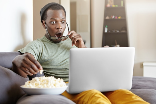 Surprised african male sitting on couch at home, eating popcorn and watching exciting tv show online on laptop computer or shocked with cliffhanger ending of detective series, keeping his mouth open