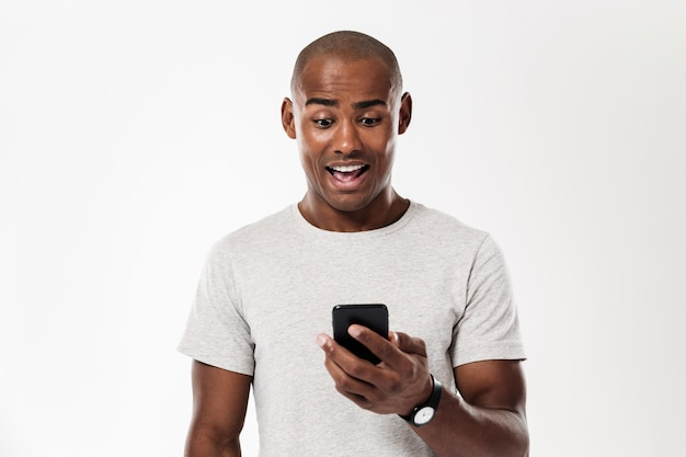 Surprised african man using smartphone
