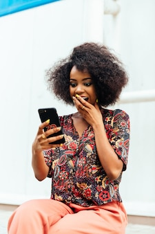 Surprised african woman, covering her mouth by hand while looking at smartphone screen