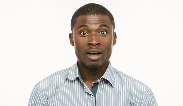 驚いたアフリカ系アメリカ人のビジネスマン。若い驚かれる男は開いた口と驚いた目でカメラを見てください。