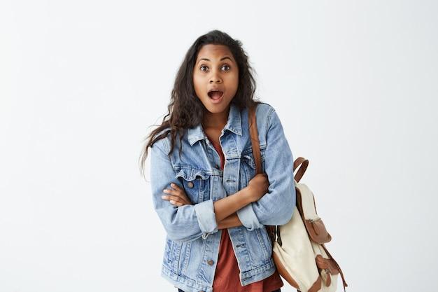 衝撃のデニムジャケットとバックパック付きの赤いtシャツを着て驚いたアフリカ系アメリカ人の女子学生、口を大きく開いて顎を下ろし、腕を折りたたんで驚かせた