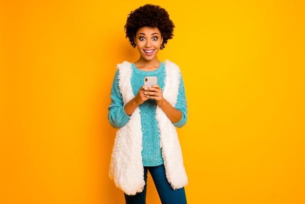 Удивленная афро-американская девушка использует смартфон поиск в блоге новости в соцсети крик вау, боже мой, носить белые пушистые синие брюки брюки бирюзовый стильный модный свитер изолированный блеск цвет стены