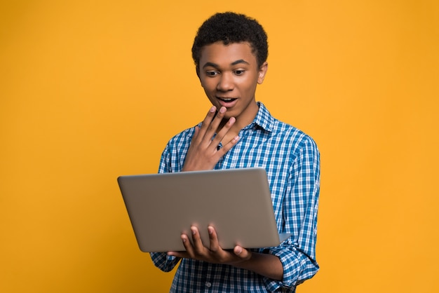 Surprised afro american teen looks at laptop screen.