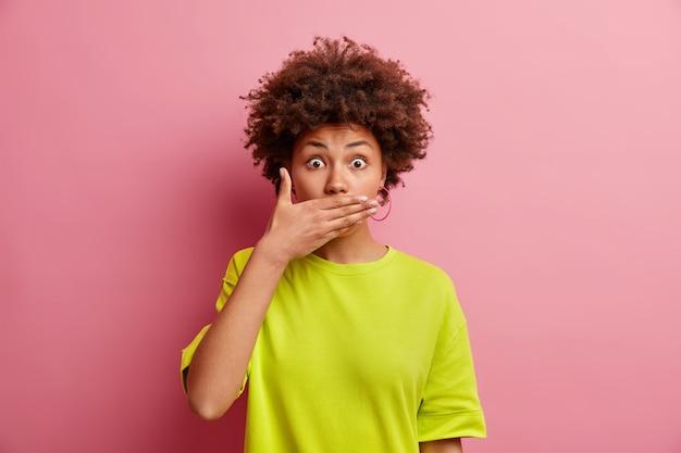 驚いたアフリカ系アメリカ人の女性は、ピンクの壁に隔離されたカジュアルなtシャツに身を包んだゴシップを聞くカメラにショックを受けた手のひらの凝視で口を無言でカバーしようとします