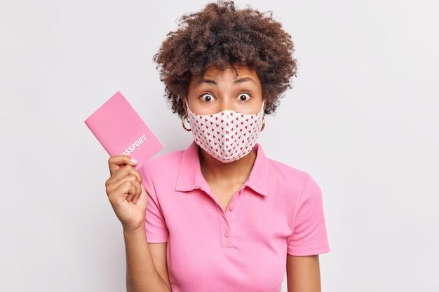 Удивленная афроамериканка с вьющимися волосами в защитной гигиенической маске держит паспорт, собираясь отправиться в путешествие во время пандемии коронавируса, узнает некоторые подробности о будущем полете, изолированном на белой стене