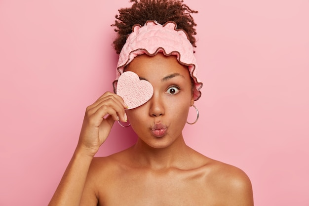Surprised afro woman covers one eye with cosmetic sponge, keeps lips rounded, bugged eyes, has beauty treatments in spa salon, has combed curly hair