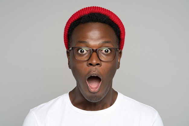 Surprised afro young man makes big eyes opens mouth widely, shocked with unprecedentedly low prices