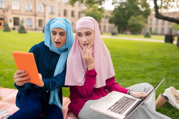 읽은 후 놀랐습니다. 인터넷에서 정보를 읽은 후 놀란 히잡을 입은 무슬림 학생들