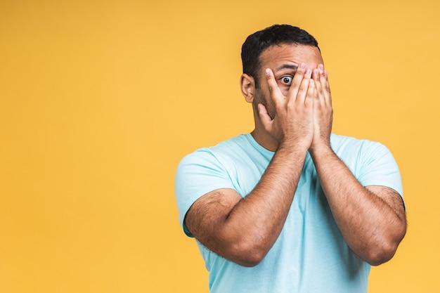黄色の背景のスタジオの肖像画の上に分離されたカジュアルで驚いたアフリカ系アメリカ人のインド人男性の男を驚かせた。人々のライフスタイルの概念。コピースペースをモックアップします。口を開いたままにします。
