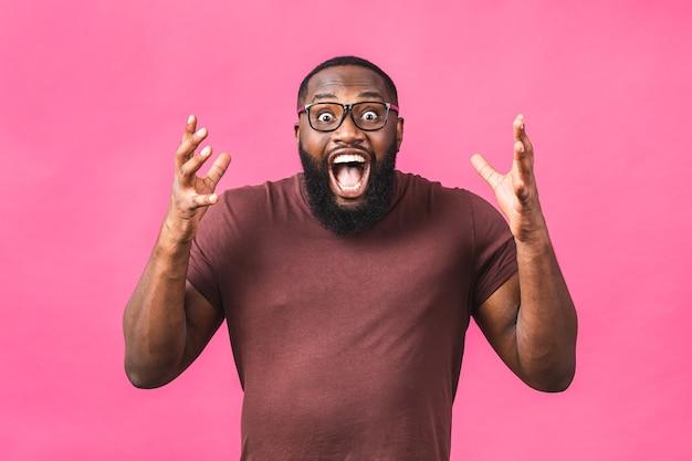 분홍색 배경 스튜디오 초상화에 격리된 캐주얼한 옷을 입은 아프리카계 미국인 남자가 놀랐습니다. 사람들이 라이프 스타일 개념입니다. 복사 공간을 비웃습니다. 입을 벌리고 있습니다.