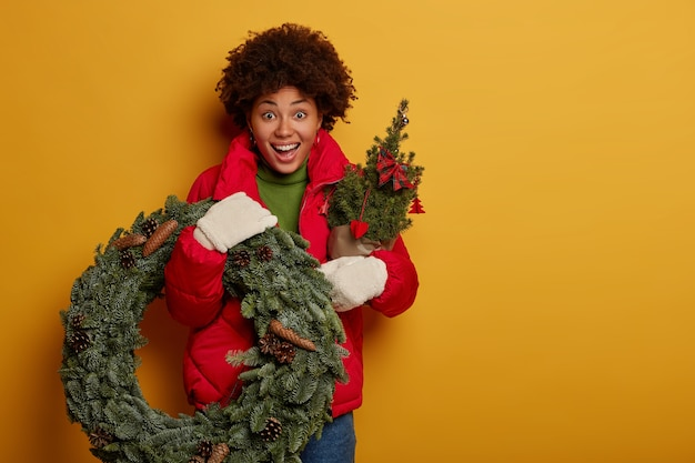 Surprised amazed afro american woman holds green wreath and firtree, has joyful expression, prepares for christmas or new year, isolated over yellow wall.