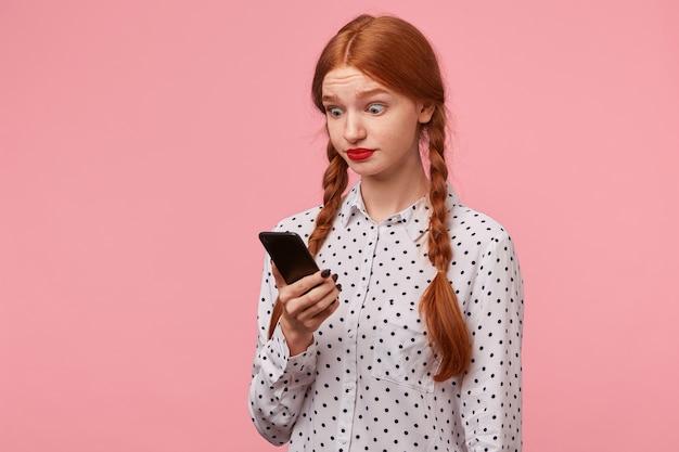 Удивленная изумленная девушка реагирует на сообщение от подруги, держа телефон в руках и глядя на него широко открытыми большими круглыми глазами, стоит пол-оборота изолированно на розовом